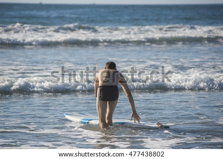 Athletic muscular man with swimsuit trunks guiding surfboard in shallow water from behind