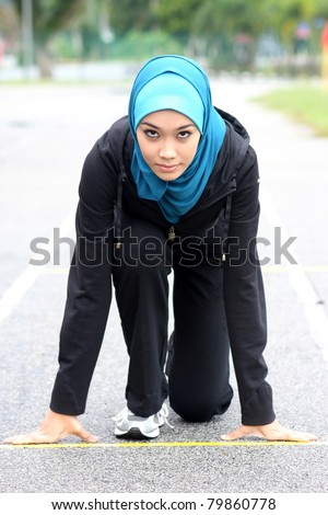 Athletic muslim woman on track starting to run - stock photo