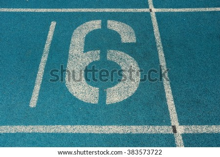 Athletic running track with number six - stock photo