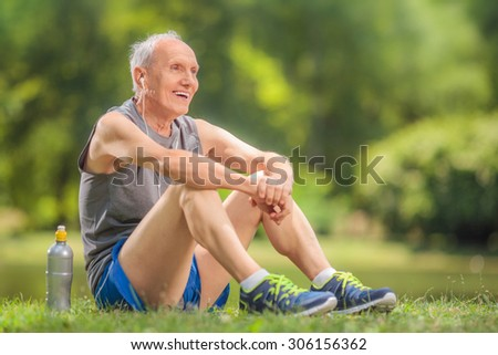 Athletic senior in sportswear sitting on grass in a park and listening to music on headphones - stock photo