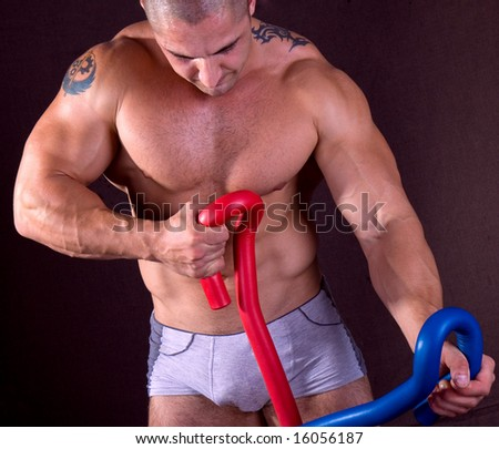 Athletic sexy male body builder doing exercise. The champion in a fitness center. - stock photo