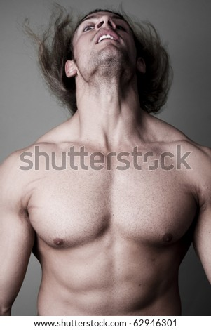Athletic sexy male body builder with the blonde long hair. on black background - stock photo