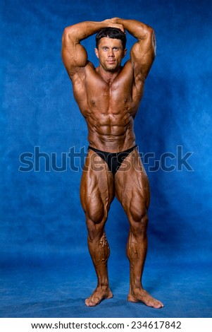 Athletic sports bodybuilder demonstrates posture. Mandatory poses bodybuilders. On a blue background - stock photo