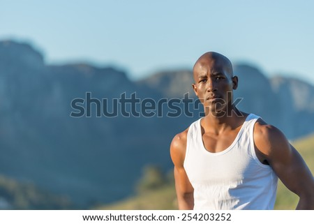 Athletic, sporty, muscular, healthy black male standing along a road outdoors with a mountain background.