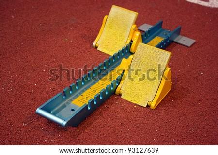 Athletic start block on dark red tartan track - stock photo