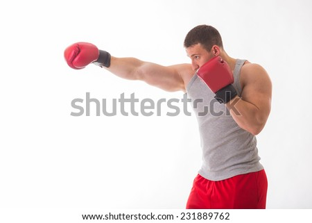 Athletic, strong guy in red boxing gloves, boxing on a white background. Sports, fitness, strength, boxing, kick, power - the concept of active fitness.