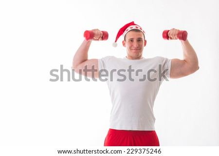 Athletic, strong man in a Christmas hat, posing on a white background. A man holding a dumbbell. Christmas, new year, fitness, sport - the concept of New Year's fitness.