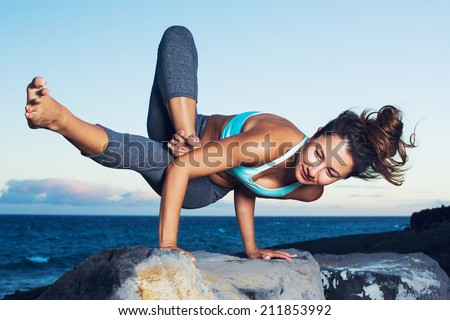 Athletic strong woman practicing difficult yoga pose outdoors - stock photo