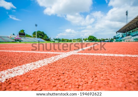 Athletic track in stadium on sunny day - stock photo