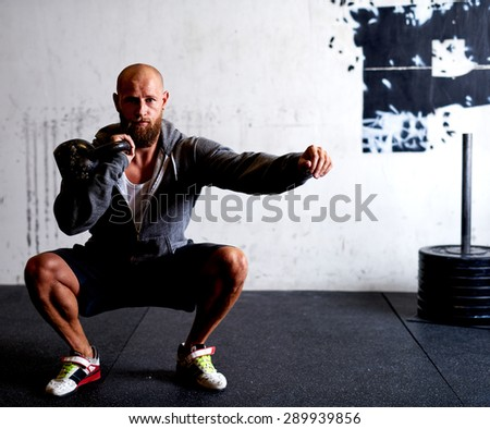 Athletic white man doing squats while lifting kettlebells - stock photo
