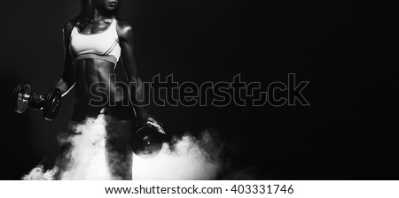 athletic woman. athletic girl with dumbbells. Studio photography. smoke effects. healthy athletic girl with massive dumbbells in his hands. working muscles. sport.dry working muscles. black and white/ - stock photo