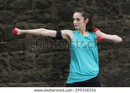 Athletic woman athletic using dumbbells. Action and healthy lifestyle concept. - stock photo