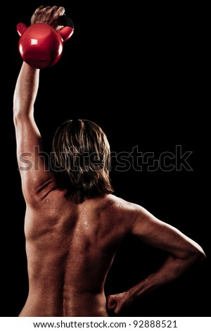 Athletic woman doing a fitness workout with Kettlebell weights for her back and arm muscles - stock photo