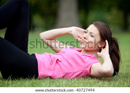 Athletic woman doing exercises for her abs outdoors - stock photo