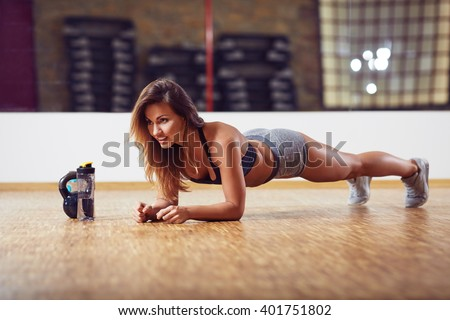 Athletic woman doing plank exercise at gym - stock photo