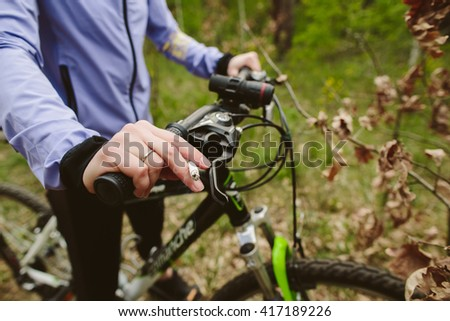Athletic woman hand in forest with bicycle and cigarette smoking