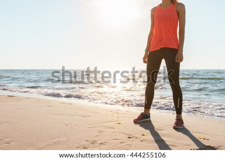 Athletic woman in red T-shirt without sleeves and sneakers standing on the beach in the morning sunshine before jogging. Concept sports lifestyle, space for text. - stock photo