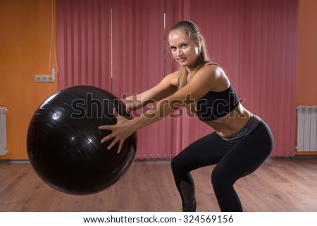 Athletic Woman in Squat Position Holding Black Fitness Ball and Smiling at the Camera. - stock photo