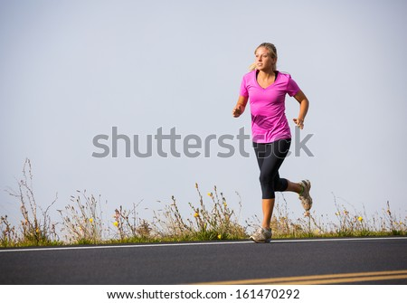 Athletic woman jogging outside, training outdoors. Running on road at sunset - stock photo