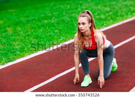 Athletic woman on track starting to run. Healthy fitness concept with active lifestyle. - stock photo