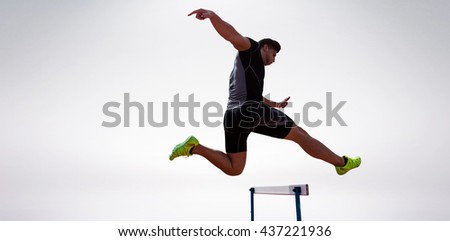Athletic woman practicing show jumping against grey background - stock photo