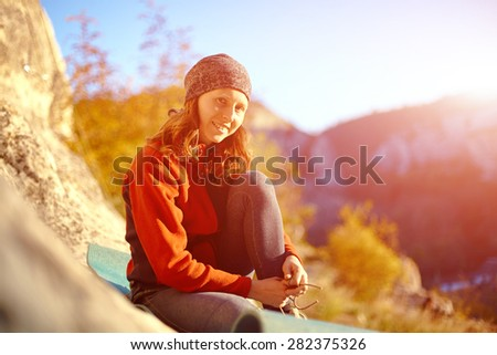 athletic woman puts shoes sitting on a rug - stock photo