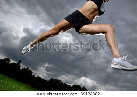 Athletic woman running before the storm - stock photo