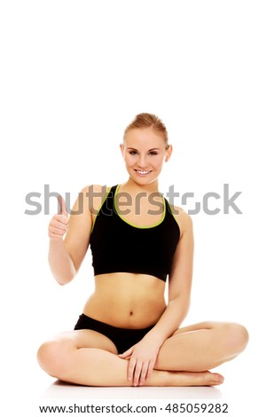 Athletic woman sitting cross legged on the floor and show thumb up