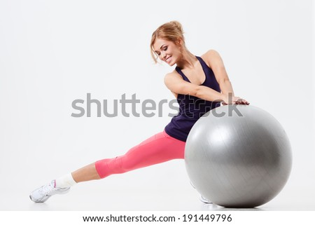 Athletic woman sitting on a gym ball on gray background - stock photo