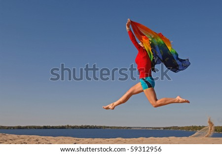 Athletic woman, wearing colourful clothes, jumps in the air with scarf in her hands. - stock photo