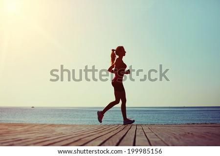 Athletic woman with a beautiful figure runs on the wooden pier on the sea and sky background, morning jog on the beach