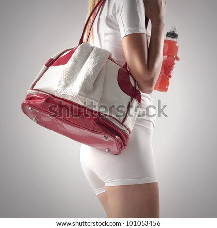 Athletic woman with a sports bag and sports drink - stock photo