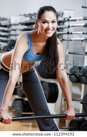 Athletic woman with dumbbells in sport centre