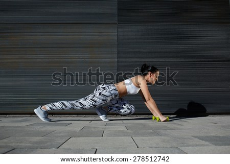 Athletic woman with perfect figure and buttocks shape stretch legs with dumbbells near copy space wall for your text message, fit female in workout gear doing push-ups on black background outdoors - stock photo