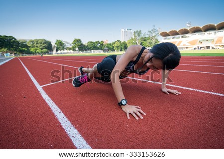 Athletic woman working out on track, mountain climber position