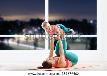athletic woman working out with little baby at fitness class in evening
