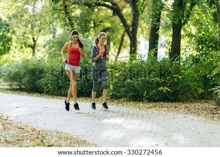 Athletic women exercising by jogging in nature