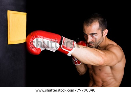 Athletic young boxer fighter punching bag over black background - stock photo