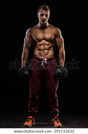 athletic young caucasian man in studio on black background with dumbellss