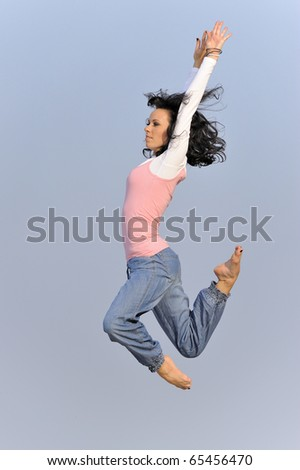 athletic young girl jumping on the beach in the Baltic Sea