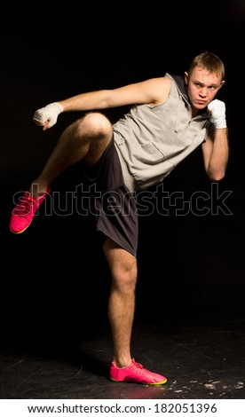 Athletic young kickboxer kicking out during a fight balancing on one foot as he readies himself to follow up with a punch from his bandaged fist - stock photo