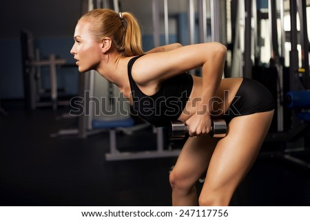 Athletic young lady doing workout with weights - stock photo