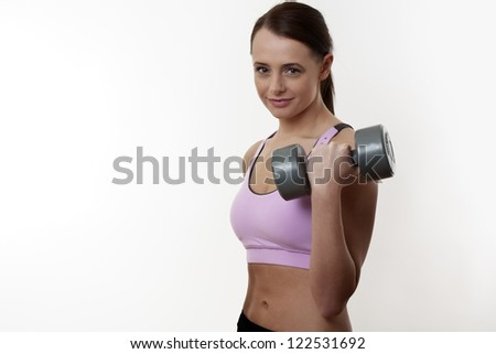 Athletic young lady doing workout with weights using dumbbells