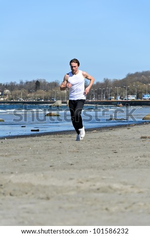 Athletic young male running on the beach - stock photo