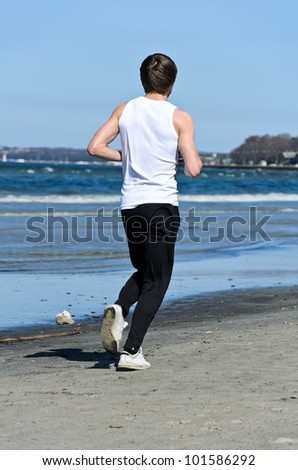 Athletic young male running on the beach. From the back - stock photo