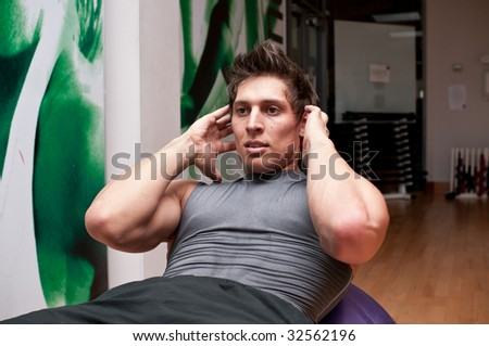 Athletic young man doing ball crunches in a gym. - stock photo
