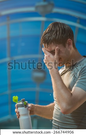 Athletic young man drinking water after hard training - stock photo