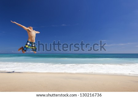 Athletic young man enjoying the summer, jumping in a tropical beach
