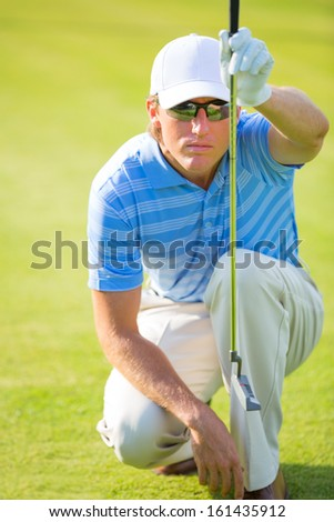 Athletic young man playing golf, lining up shot to hole - stock photo