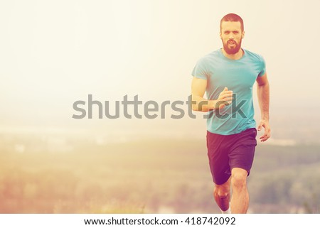 Athletic young man running in the nature. Healthy lifestyle - stock photo